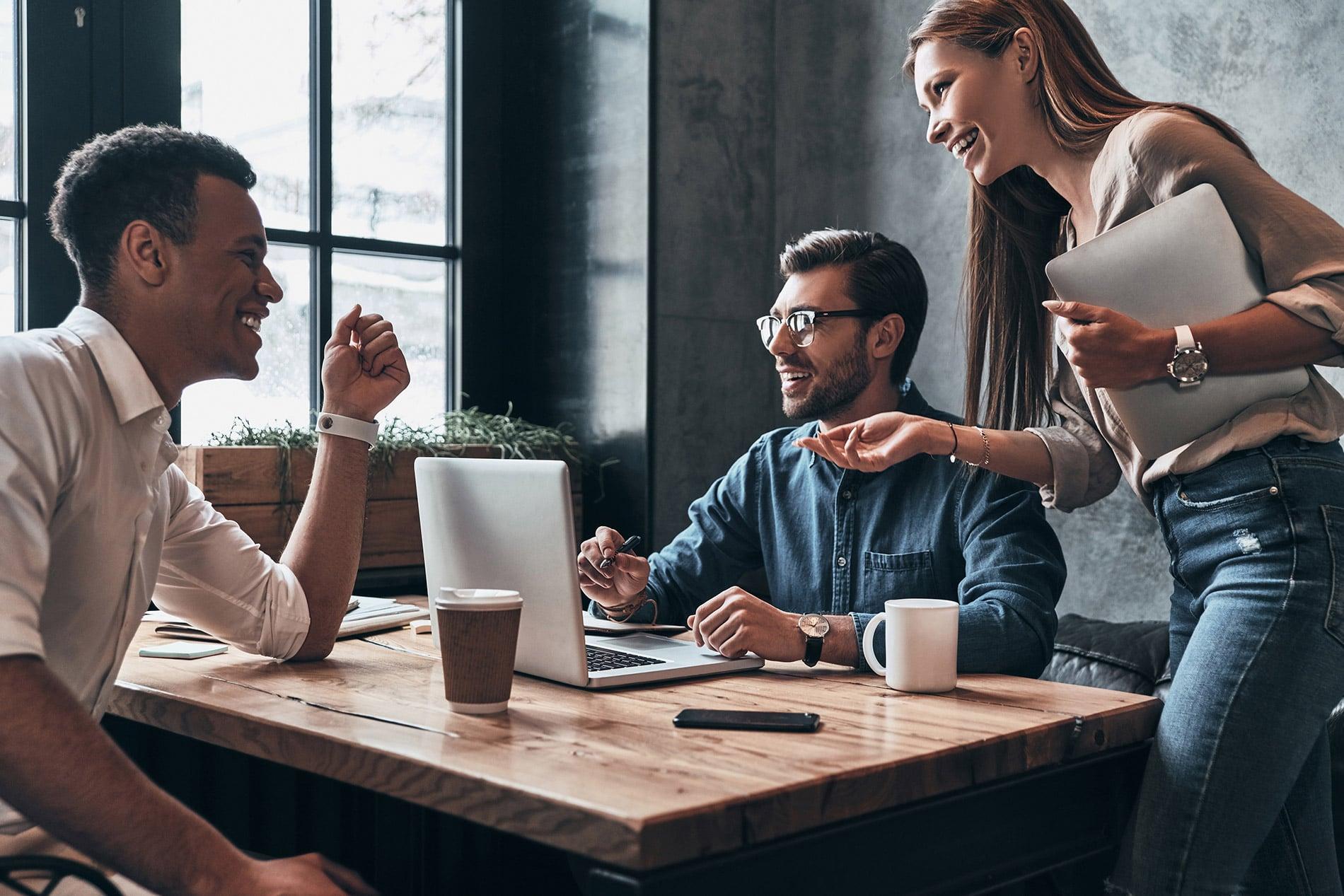 Deux hommes et une femme discutant de travail sur un bureau en bois -
