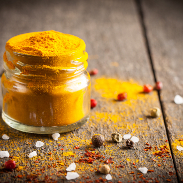Pot de curry jaune sur table en bois avec du poivre frais - gamme épicerie salé