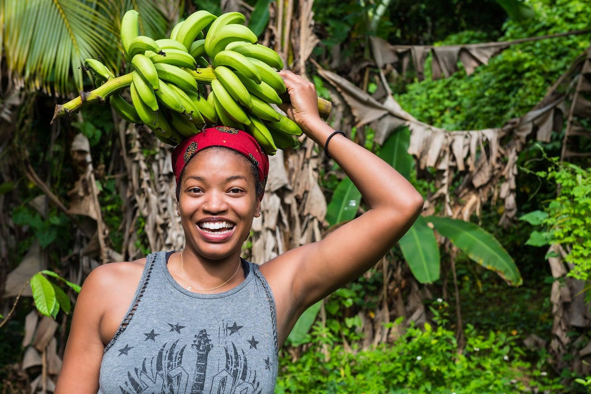 Photo Femme metisse souriante avec régime de banane posé sur la tête